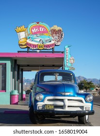 Kingman, Arizona / USA - 21 Oct 2019: A blue vintage Chevrolet 3100 farm truck sits outside a colourful Route 66 diner with pink / green paint, neon burger and root beer sign against a clear blue sky.