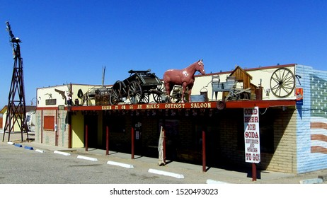 """KINGMAN, ARIZONA/USA- May 1, 2016: Mike's Route 66 Outpost Saloon features Old West themed roof items to attract the attention of travelers on the """"Mother Road""""."""