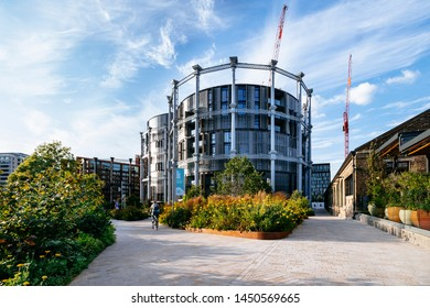 King's Cross London, UK, July 12, 2019: Granary Square urban landscape design, openspace pedestrian walkway with residential building iron colums structure gas holder in the background