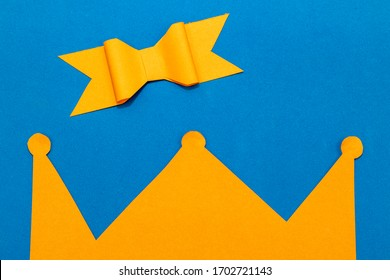 Kings day concept for the Dutch fest called Koningsdag. With an orange paper crown and an orange paper bow on a blue background. Room for copy.