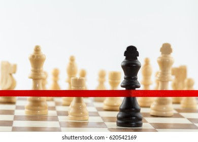 The King's figure crossing the red finish ribbon. Chess business leadership and success concept