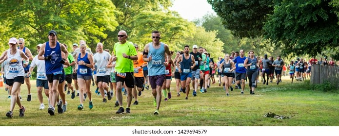 Kings Park, New York, USA - 17 June 2019: runners moments after the start of the summer series 10K running across the grass at Sunken Meadow State PArk.