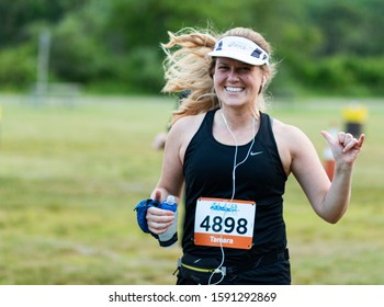 Kings Park, New York, USA - 17 June 2019: Runner racing a 10K is smiling and giving hang loose sign while carrying water bottle in the other hand during the Sunken Meadow State Park Summer Series