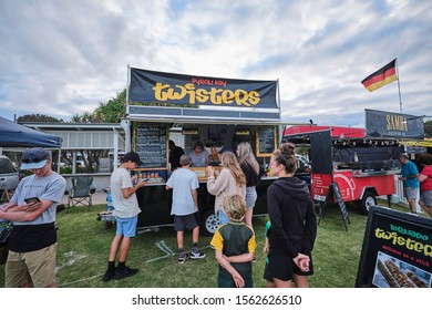 Kingscliff, NSW / Australia - November 1st 2019: Kingscliff night markets with food being served and adults and children waiting to watch a movie in open air cinema