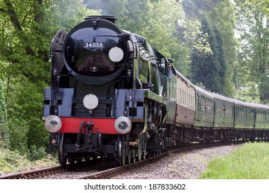 KINGSCOTE, SUSSEX/UK - MAY 23 : Rebuilt Bulleid Light Pacific No. 34059 steam locomotive near Kingscote Station on May 23, 2009. Unidentified people.