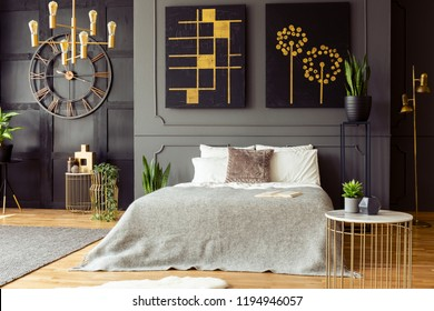 King-size bed with bright sheets standing in real photo of dark bedroom interior with gold lamps, fresh plants, simple paintings and wainscoting on wall