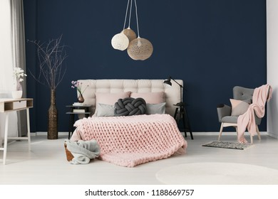 King-size bed with soft bedhead, knot grey cushion and powder pink blanket standing in real photo of elegant hotel room interior with handmade lamps and dark blue wall