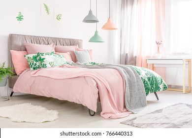 King-size bed with soft bedhead and pastel pink bedding in feminine room with window
