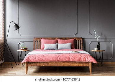 A king-size bed standing in a bedroom interior between bedside tables and with a black lamp next to it