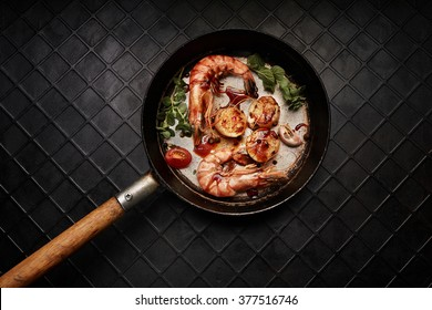 King-size shrimps and 3 scallops on a old black pan. Top view.
