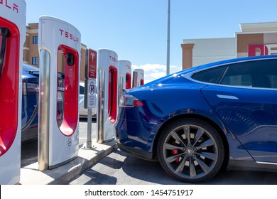 KINGSTON, CANADA - June 7, 2019: Blue Tesla Model S plugged-in, charging at Tesla's Kingston, Ontario Supercharger Station.