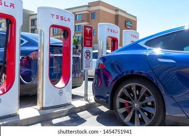 KINGSTON, CANADA - June 7, 2019: Blue Tesla Model S and Tesla Model X at Tesla Supercharger on a bright sunny day.