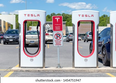 KINGSTON, CANADA - June 7, 2019: Tesla Supercharger Stalls in Kingston, Ontario with parking restriction signs and blue Tesla Model S charging in the background.