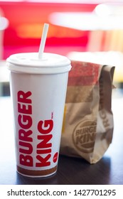 KINGSTON, JAMAICA - JUNE 15, 2019 - BURGER KING SANDWICH PACKED IN A BROWN PAPER BAG BESIDE A CUP OF SODA ON A TABLE