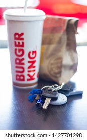 KINGSTON, JAMAICA - JUNE 15, 2019 - BURGER KING SANDWICH PACKED IN A BROWN PAPER BAG BESIDE A CUP OF SODA ON A TABLE WITH A SET OF CAR KEYS.