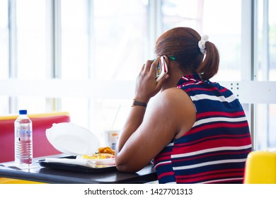 KINGSTON, JAMAICA - JUNE 15, 2019 - WOMAN TALKING ON HER CELLPHONE WHILE HAVING BREAKFAST AT A FAST FOOD RESTAURANT