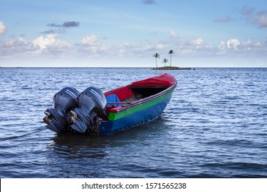 KINGSTON / JAMAICA - SEPTEMBER 28, 2019: Fishing Boat pointed towards an Island with coconut trees.