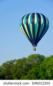 Kingston, Rhode Island/USA- July 23, 2016: A vertical image of a blue, green and yellow hot air balloon, coming in for a landing over the treetops, at a hot air balloon festival.