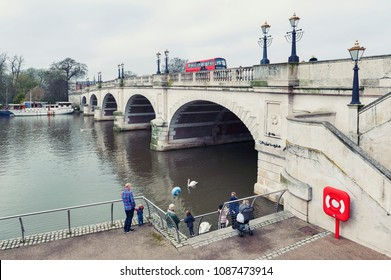 Kingston upon Thames, United Kingdom - April 2018: Tourists feeding waterbirds and swans at Kingston Bridge on Riverside Walk promenade by the River Thames in Kingston, England