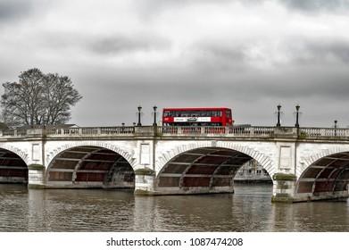 Kingston upon Thames, United Kingdom - April 2018: New Routemaster Double-decker bus crossing Kingston Bridge over the River Thames in Kingston, England