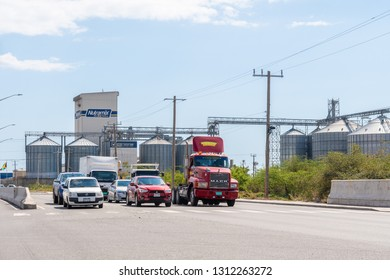 Kingston/Saint Andrew, Jamaica - February 05 2019: Beyond the vehicles is Newport Mills Limited, a member of the Caribbean Broilers (CB) Group, the most modern feed mill in the Caribbean to date.