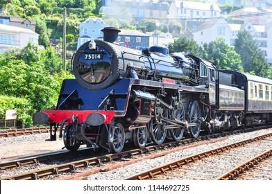 KINGSWEAR, DEVON/UK - June 27, 2018. Standard Class 4 steam locomotive leaving Kingswear, Dartmouth Steam Railway, South Devon, England