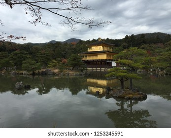 """Kinkaku-ji Or """"Temple of the Golden Pavilion"""", Officially Named Rokuon-ji, Literally """"Deer Garden Temple""""), is a Zen Buddhist temple in Kyoto, Japan.  Golden Pagoda On A Cloudy Day with Pond / Lake."""