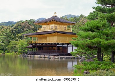 Kinkakuji temple, also known as the Golden Pavilion,  in Kyoto, Japan. Beautiful Zen temple with the top two floors coated in gold leaf. With a reflection in the water at the front.