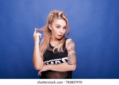 Kinky blonde tattooed woman looking straight to the camera on blue background