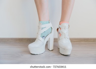 Kinky women`s legs in mismatched colorful cotton socks on white background. Female feet in eccentric white leather fashionable  modern shoes on high heels. Unrecognizable impudent cocky teenager