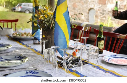 Kinna, Sweden, 19 June 2009: Preparation of the food and decoration on Midsummer (Midsommar). Swedish flag and glasses of sprits and flowers are most important. Swedish secret national day.