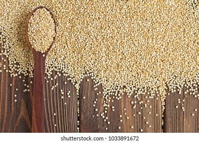 Kinoa seeds in wooden spoon on wooden table, organic