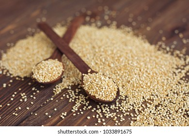 Kinoa seeds in wooden spoons on wooden table