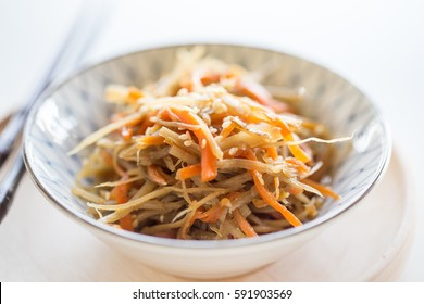 Kinpira gobo, chopped burdock root and carrot cooked in sugar and soy sauce.