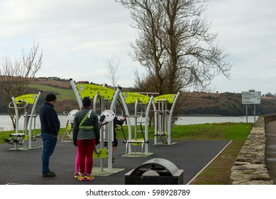 Kinsale, Ireland - February 12, 2017: A sport minded family inspecting modern exercise equipment at a fitness park in the waterfront area in Kinsale in southern Ireland.
