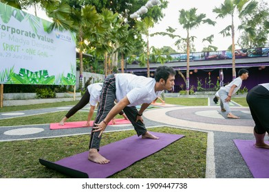 Kintamani, Bali, Indonesia - 28 June 2019: A man doing yoga pose bending down in a yoga retreat.