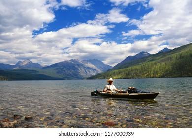 KINTLA LAKE, GLACIER NATIONAL PARK, MONTANA, USA - September 9, 2018: Kayaker rows to the shore of Kintla Lake