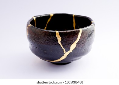 Kintsugi black raku chawan bowl. Gold cracks restoration on old Japanese pottery restored with the antique restoration technique.The unique beauty of imperfections.