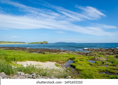 Kintyre peninsula shores, green grass and blue sky at nice summer day in Scotland