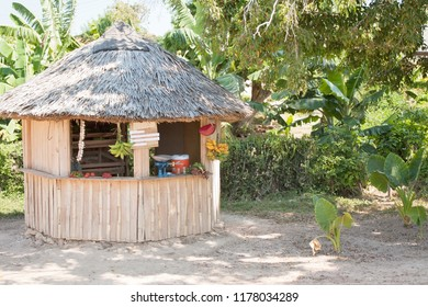 A kiosk selling tropical fruit and vegetables  in the shoulder of a road in Cuba, surrounded by tropical vegetation.