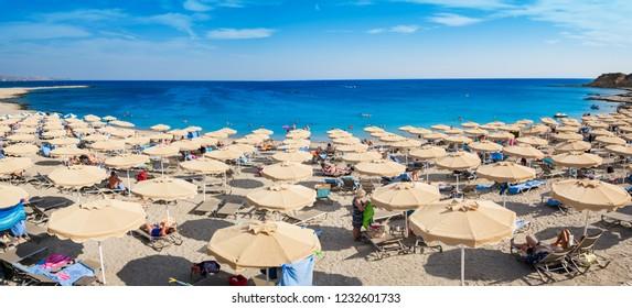 Kiotari beach with umbrellas and holiday-makers in village of Kiotari - PANORAMA (Rhodes, Greece)