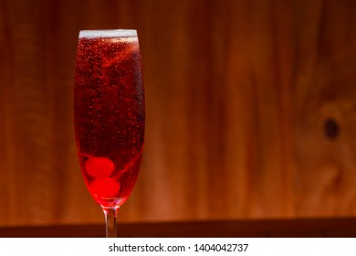Kir royal cocktail with cherry on wood background