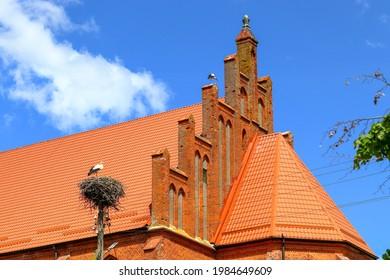 A kirche in Krasnoznamensk, Kaliningrad region and a white stork's nest on a pillar - Shutterstock ID 1984649609