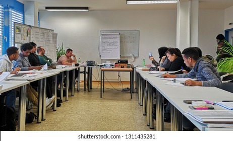 Kirchheimbolanden / Germany - January 08 2019: Groups of adult students of different nationalities and ages,learning german language by immersion in the classroom,writing in notebooks,selective focus