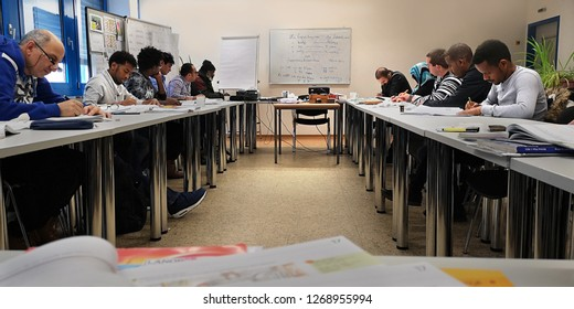 Kirchheimbolanden / Germany - November 21 2018: Groups of adult students of different nationalities and ages,learning german language by immersion in the classroom,writing in notebooks,selective focus