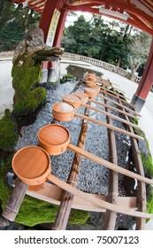 KIRISHIMA, JAPAN - FEBRUARY 18: Bamboo wood ladles resting on the purification fountain of Kirishima Shrine, February 18, 2011 in Kirishima, Kagoshima, Japan.