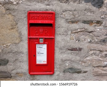 Kirkby Lonsdale, Cumbria, UK -  April 4 2019: Red metal British Royal Mail post box  mounted in an old stone wall
