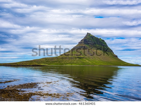 Kirkjufell (Church mountain) mountain reflected on the wavy waters of the Grundar fjord near the town of Grundarfjordur, Snaefellnes peninsula, Iceland