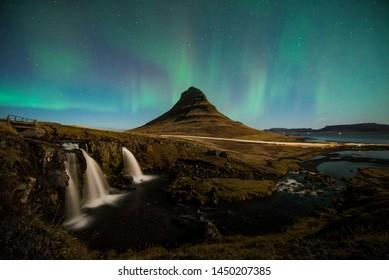 Kirkjufell mountain and kirkjufell waterfall with green northern light polar borealis in background.