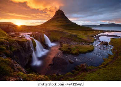 Kirkjufell mountain and waterfalls under dramatic cloudy sky